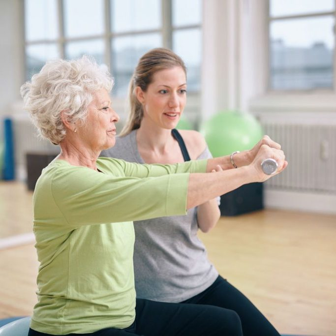 34387158 - senior woman being assisted by instructor in lifting dumbbells at gym. senior woman training in the gym with a personal trainer at rehab.