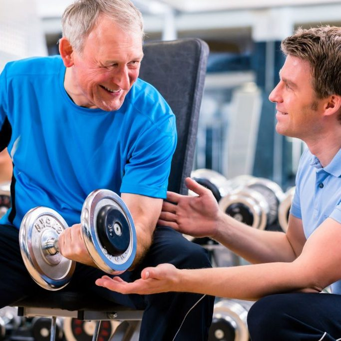 41112533 - senior man and trainer at exercise in gym with dumbbell weights